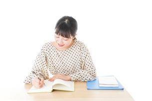 机で勉強をする若い女性の写真素材 [FYI04715148]