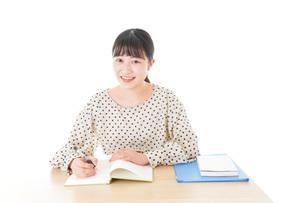 机で勉強をする若い女性の写真素材 [FYI04715151]