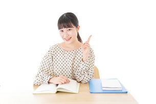 机で勉強をする若い女性の写真素材 [FYI04715155]