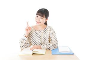 机で勉強をする若い女性の写真素材 [FYI04715158]