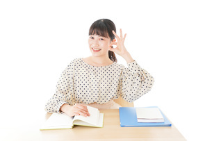 机で勉強をする若い女性の写真素材 [FYI04715164]