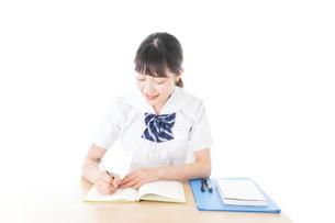 机で勉強をする制服姿の女子学生の写真素材 [FYI04715180]