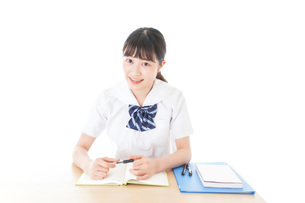 机で勉強をする制服姿の女子学生の写真素材 [FYI04715182]
