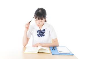 机で勉強をする制服姿の女子学生の写真素材 [FYI04715201]