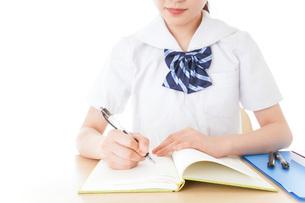机で勉強をする制服姿の女子学生の写真素材 [FYI04715202]