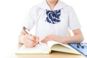 机で勉強をする制服姿の女子学生の写真素材 [FYI04715205]