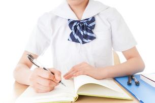 机で勉強をする制服姿の女子学生の写真素材 [FYI04715209]