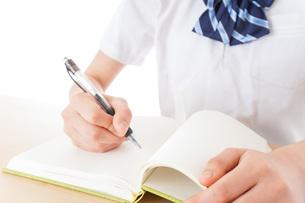 机で勉強をする制服姿の女子学生の写真素材 [FYI04715214]