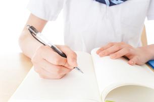 机で勉強をする制服姿の女子学生の写真素材 [FYI04715217]