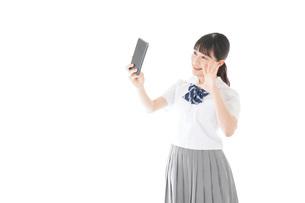 スマホを使う制服姿の女子学生の写真素材 [FYI04715272]