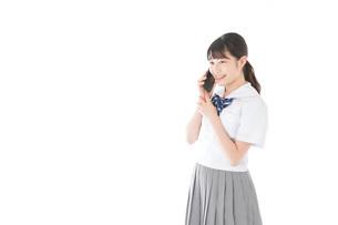 スマホを使う制服姿の女子学生の写真素材 [FYI04715273]