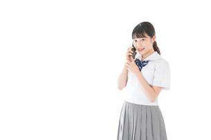 スマホを使う制服姿の女子学生の写真素材 [FYI04715277]