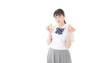 おやつを食べる制服姿の女子学生の写真素材 [FYI04715294]