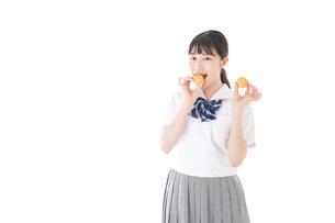 おやつを食べる制服姿の女子学生の写真素材 [FYI04715295]