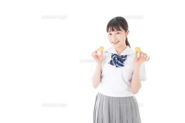 おやつを食べる制服姿の女子学生の写真素材 [FYI04715301]