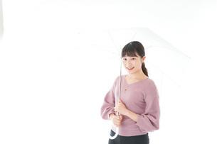 傘をさす若い女性の写真素材 [FYI04715399]