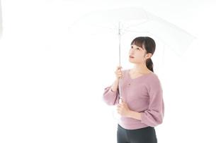 傘をさす若い女性の写真素材 [FYI04715407]