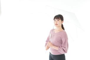 傘をさす若い女性の写真素材 [FYI04715409]