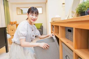 棚の片付けをする若い女性の写真素材 [FYI04715445]