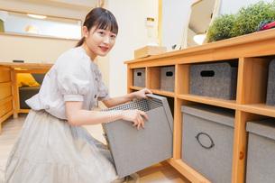 棚の片付けをする若い女性の写真素材 [FYI04715457]