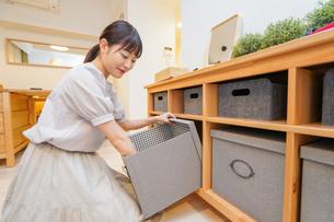 棚の片付けをする若い女性の写真素材 [FYI04715461]
