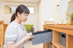 棚の片付けをする若い女性の写真素材 [FYI04715468]