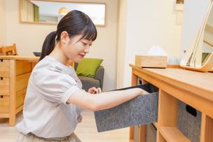 棚の片付けをする若い女性の写真素材 [FYI04715469]