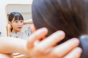 髪のセットをする若い女性の写真素材 [FYI04715474]
