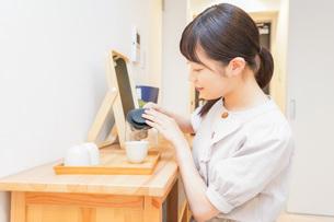 お茶を入れる若い女性の写真素材 [FYI04715481]