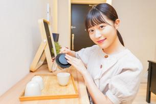 お茶を入れる若い女性の写真素材 [FYI04715486]