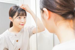 髪のセットをする若い女性の写真素材 [FYI04715489]