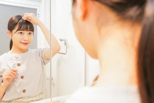 髪のセットをする若い女性の写真素材 [FYI04715491]