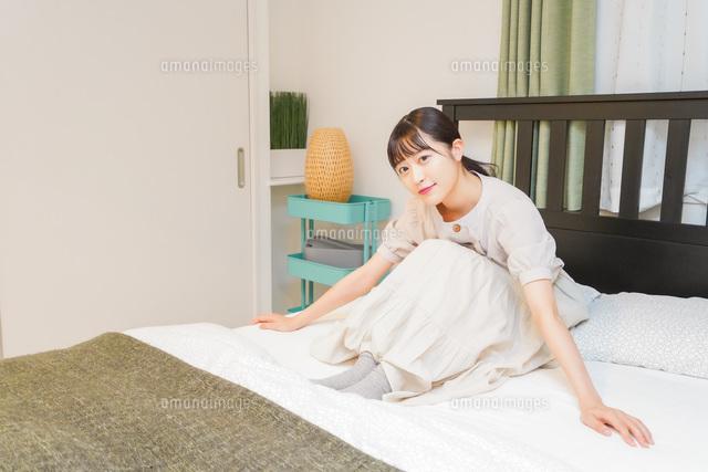 ベッドでリラックスをする若い女性の写真素材 [FYI04715530]