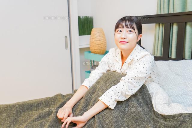 ベッドでリラックスをする若い女性の写真素材 [FYI04715543]