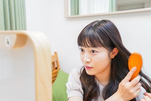髪のセットをする若い女性の写真素材 [FYI04715669]