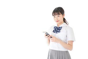 スマートフォンを使う若い女子学生の写真素材 [FYI04715890]