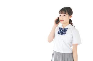スマートフォンを使う若い女子学生の写真素材 [FYI04715899]