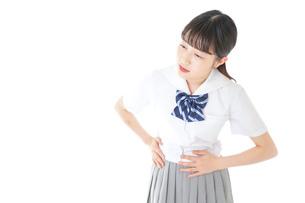 生理痛に苦しむ制服を着た女子学生の写真素材 [FYI04715926]