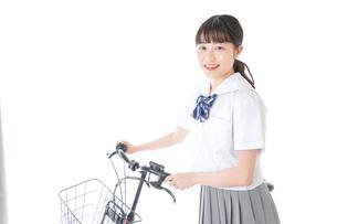 自転車通学をする若い女子学生の写真素材 [FYI04715946]