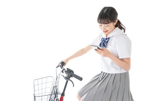 自転車でスマホを使う若い学生の写真素材 [FYI04715979]