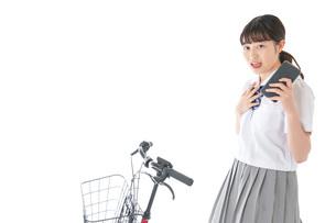 自転車でスマホを使う若い学生の写真素材 [FYI04715981]
