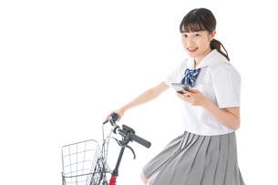 自転車でスマホを使う若い学生の写真素材 [FYI04715982]