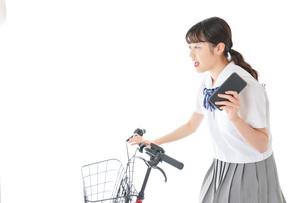 自転車でスマホを使う若い学生の写真素材 [FYI04715986]