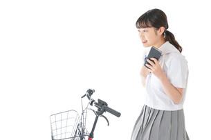 自転車でスマホを使う若い学生の写真素材 [FYI04715990]