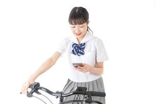 自転車でスマホを使う若い学生の写真素材 [FYI04716018]