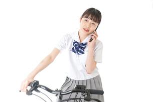 自転車でスマホを使う若い学生の写真素材 [FYI04716019]