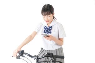 自転車でスマホを使う若い学生の写真素材 [FYI04716020]