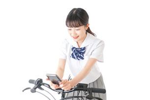 自転車でスマホを使う若い学生の写真素材 [FYI04716022]