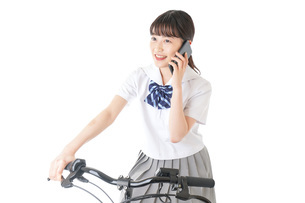 自転車でスマホを使う若い学生の写真素材 [FYI04716024]