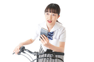 自転車でスマホを使う若い学生の写真素材 [FYI04716025]